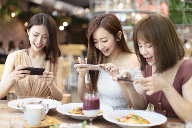 Freunde, die Telefon des Abendessens und des Aufpassens intelligentes im Restaurant haben stockbilder