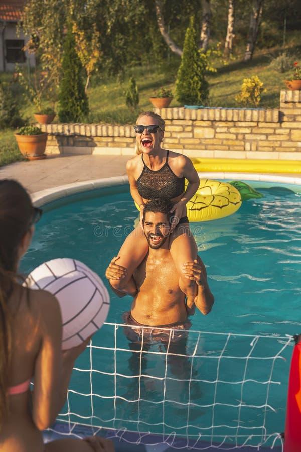 Freunde, die Volleyball im Swimmingpool spielen stockbild