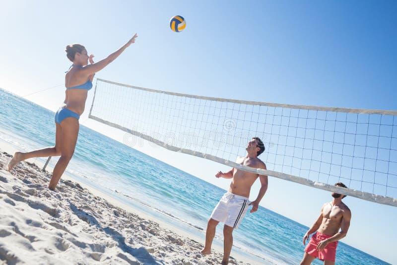 Freunde, die Volleyball spielen lizenzfreie stockbilder