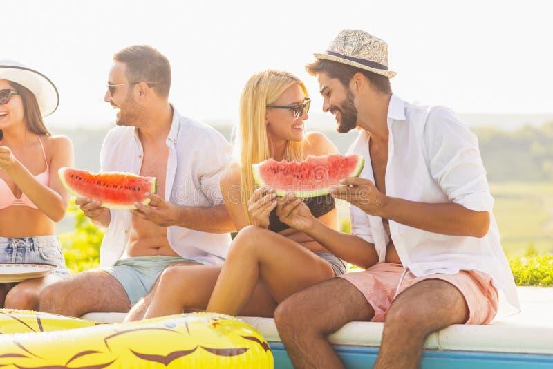 Freunde, die Wassermelone durch das Pool essen lizenzfreie stockfotos