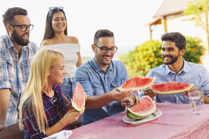 Freunde, die Wassermelone essen lizenzfreie stockfotografie