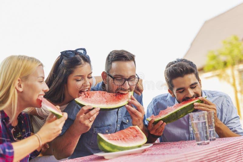 Freunde, die Wassermelonenscheiben essen lizenzfreie stockbilder