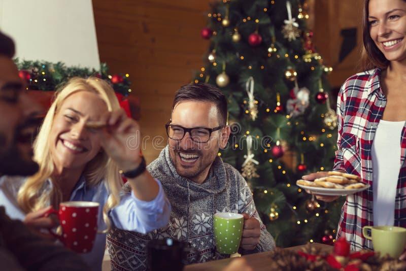 Freunde, die Weihnachtsplätzchen essen stockbilder