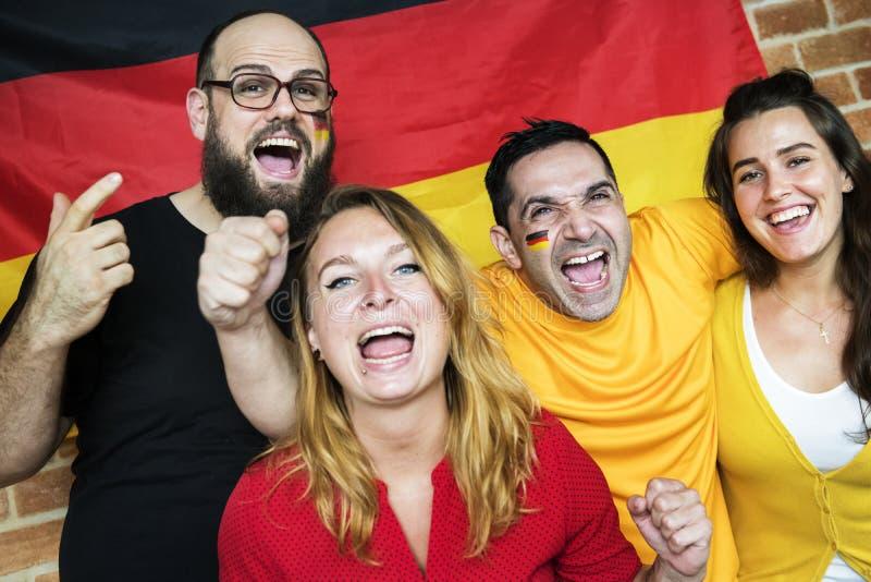 Freunde, die Weltcup mit gemalter Flagge zujubeln lizenzfreies stockfoto