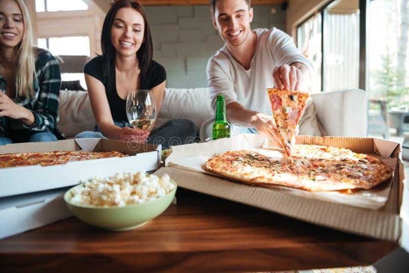 Freunde, die zu Hause geschmackvolle Pizza beim Haben einer Partei essen stockbilder