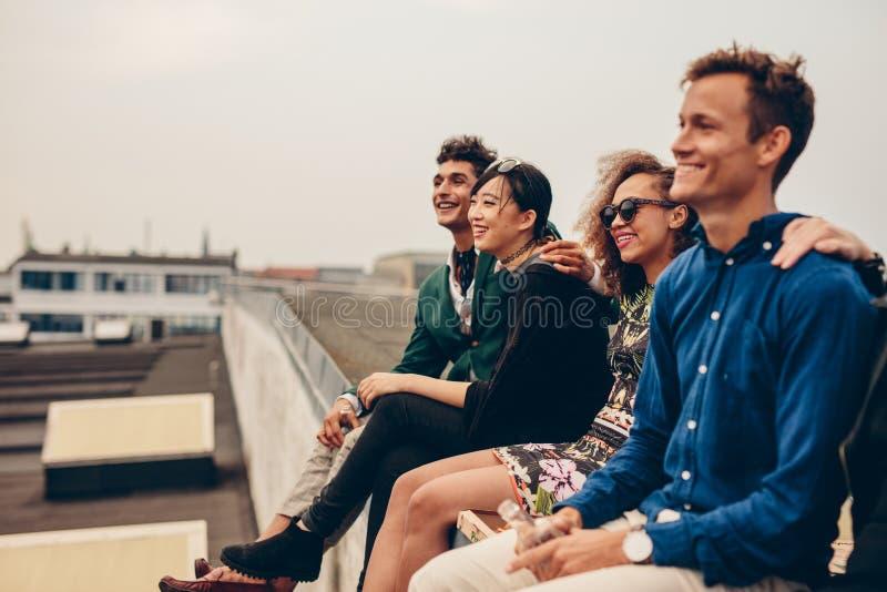Freunde, die zusammen auf Dachspitze sitzen stockfotografie
