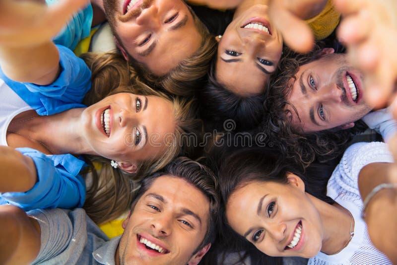 Freunde, die zusammen in einem Kreis liegen stockbild