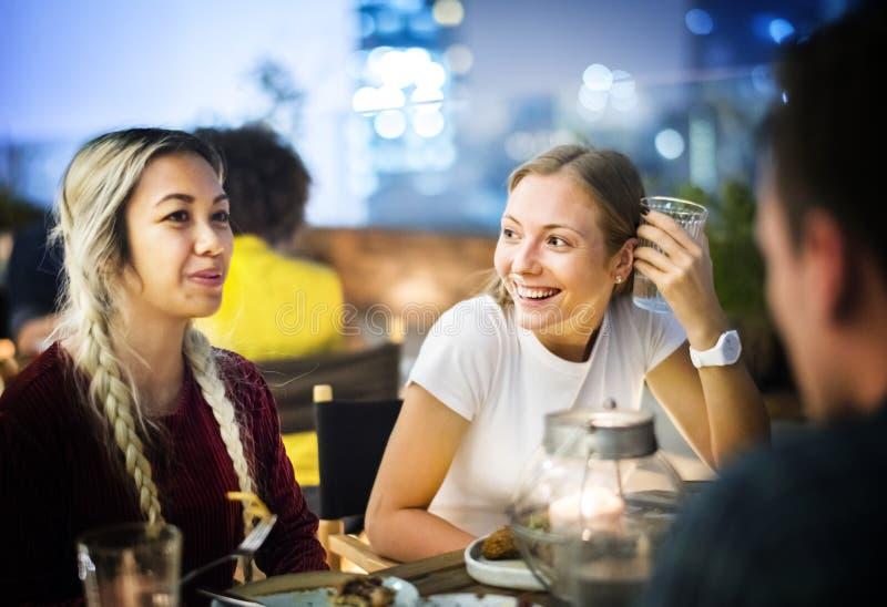 Freunde, die zusammen an einer Dachspitzenstange zu Abend essen stockfoto