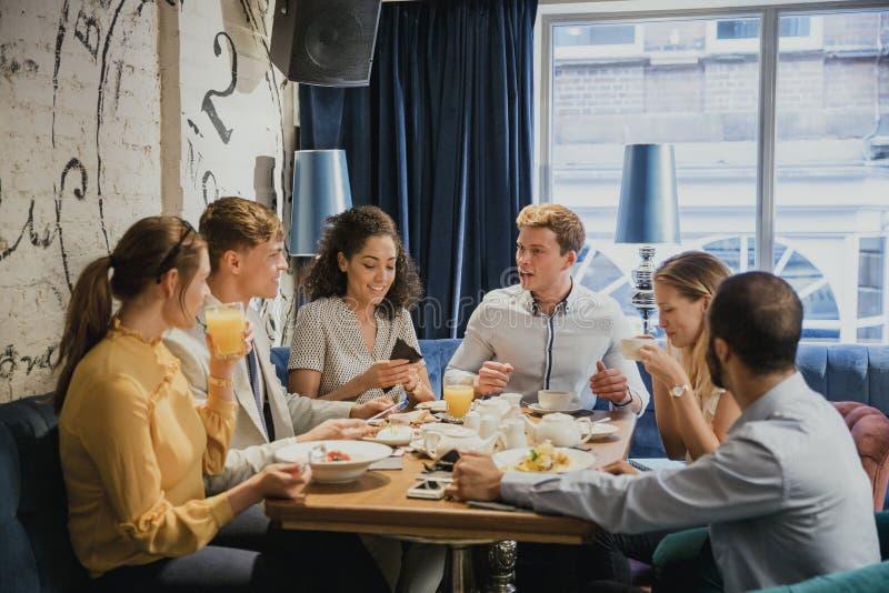 Freunde, die zusammen Frühstück genießen lizenzfreies stockbild