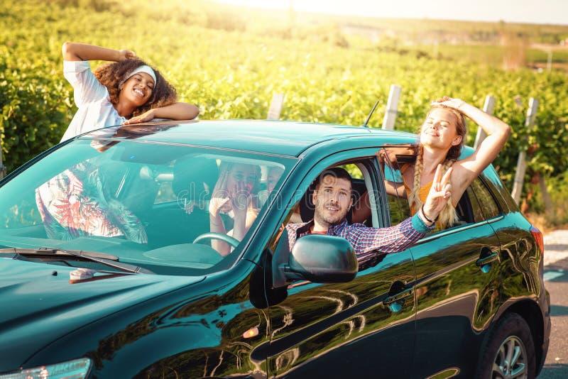 Freunde, die zusammen Landschaft der Autoreise eines Sommers genießen Frauen und Mann, die das Lächeln und das Schauen aus Fenste lizenzfreies stockfoto
