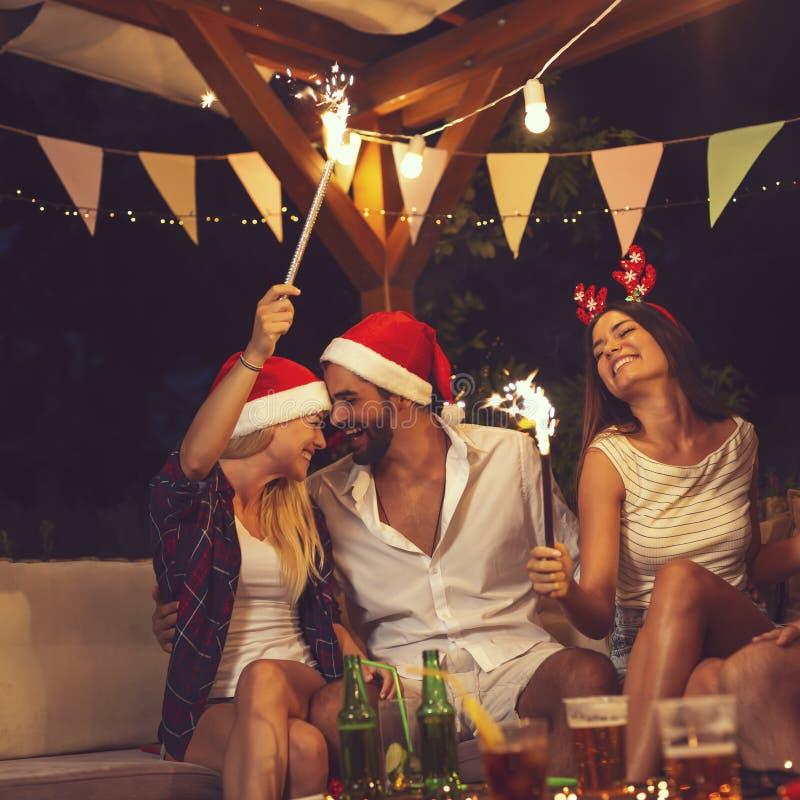 Freunde an einer Partei des neuen Jahres lizenzfreie stockbilder