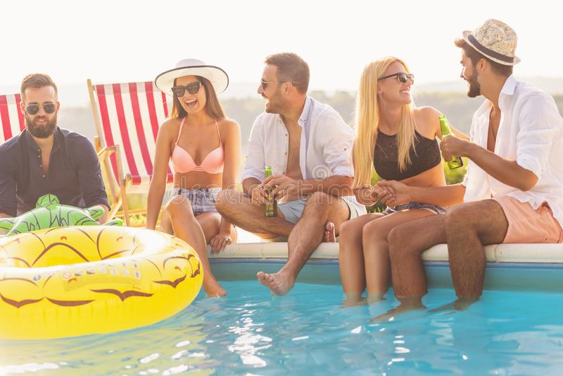 Freunde an einer schwimmenden Pool-Party lizenzfreie stockfotos
