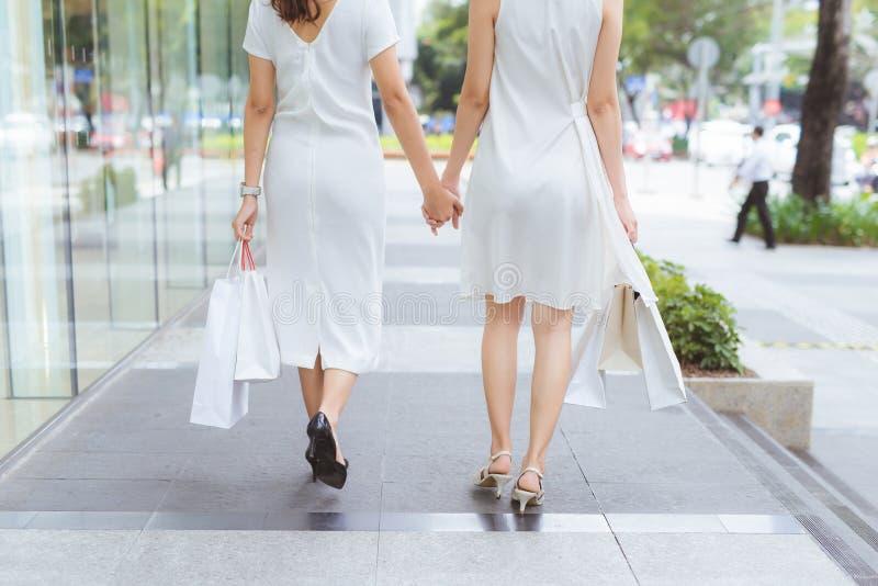Freunde gehen Weg mit zwei jungen Frauen auf Einkaufszentrum mit Taschen stockfotografie