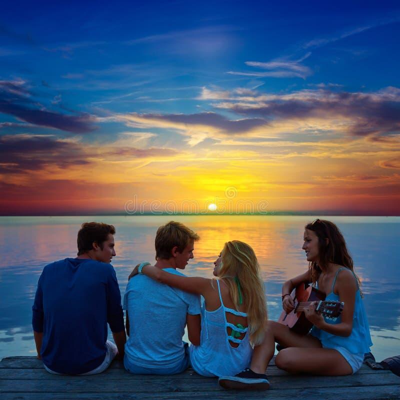 Freunde gruppieren das Spielen der Gitarre im Sonnenuntergangpier an der Dämmerung stockfoto