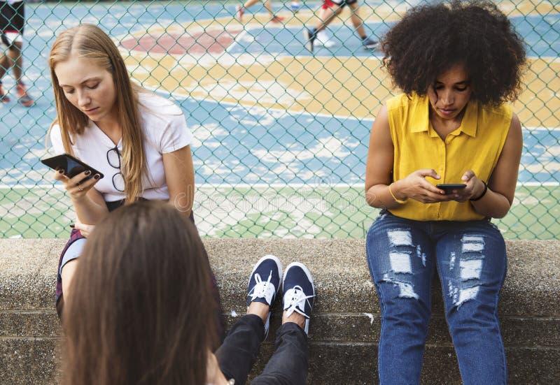 Freunde im Park unter Verwendung der Smartphones lizenzfreies stockbild