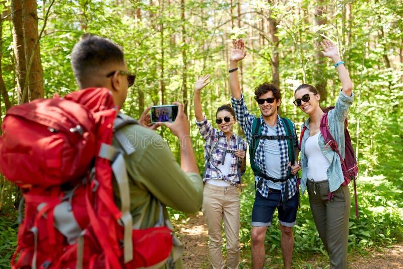 Freunde mit den Rucksäcken, die auf Wanderung fotografiert werden stockfoto
