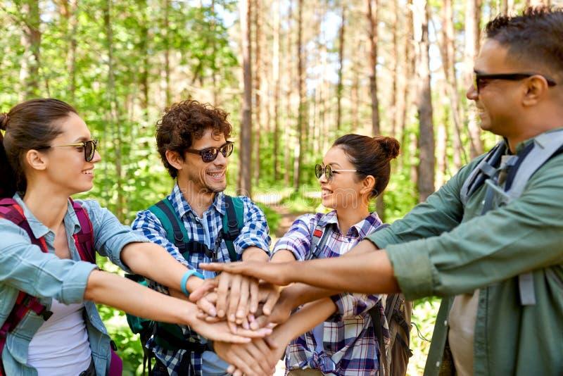 Freunde mit den Rucksäcken, die Hände im Wald stapeln lizenzfreie stockfotografie
