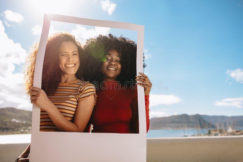 Freunde mit Fotorahmen lizenzfreies stockfoto