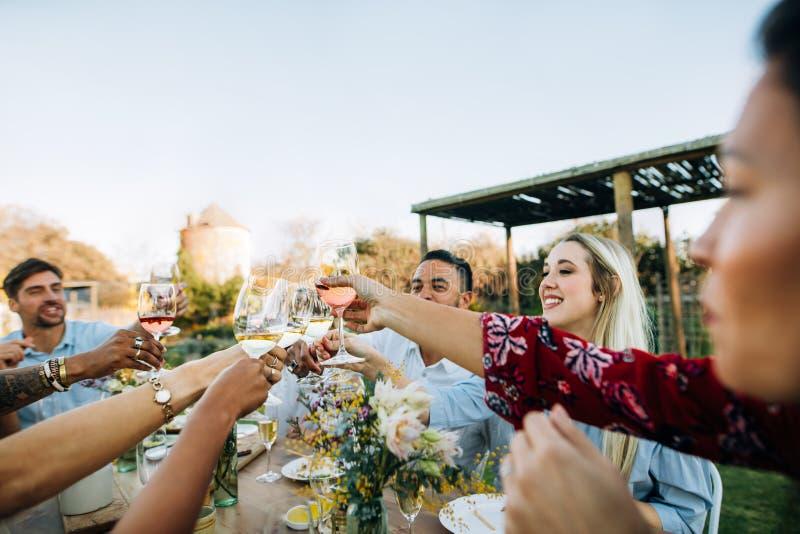 Freunde mit Getränken während der Mittagessenpartei stockfoto