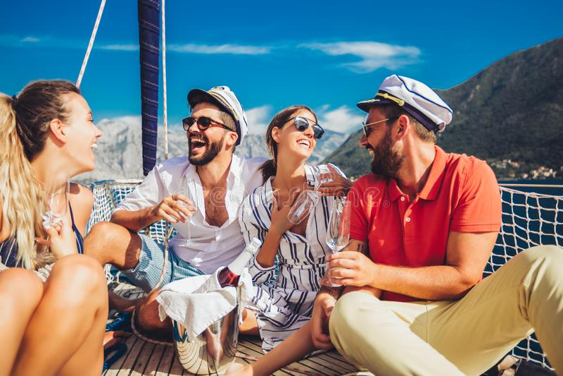 Freunde mit Gl?sern Champagner auf Yacht Ferien, Reise, Meer, Freundschaft und Leutekonzept lizenzfreie stockbilder