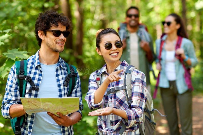 Freunde mit Karte und Rucksäcke, die im Wald wandern stockbilder