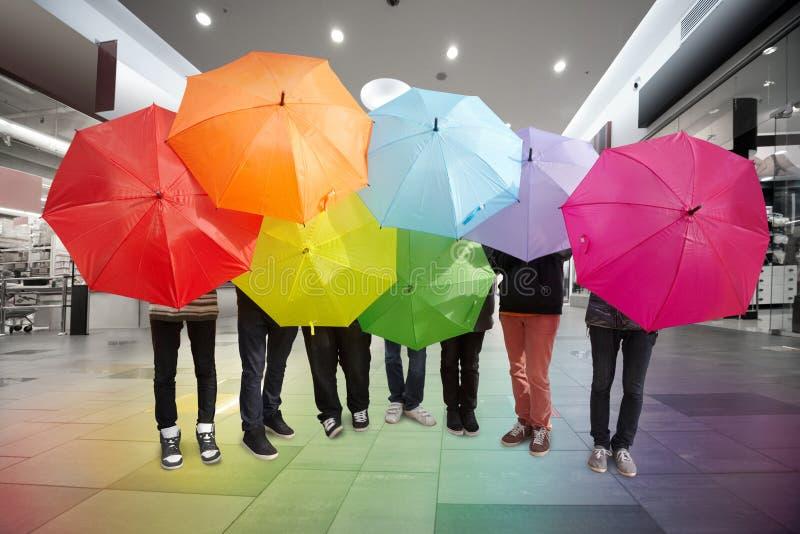 Freunde mit Regenschirmen in der Halle der handelnmitte stockfoto
