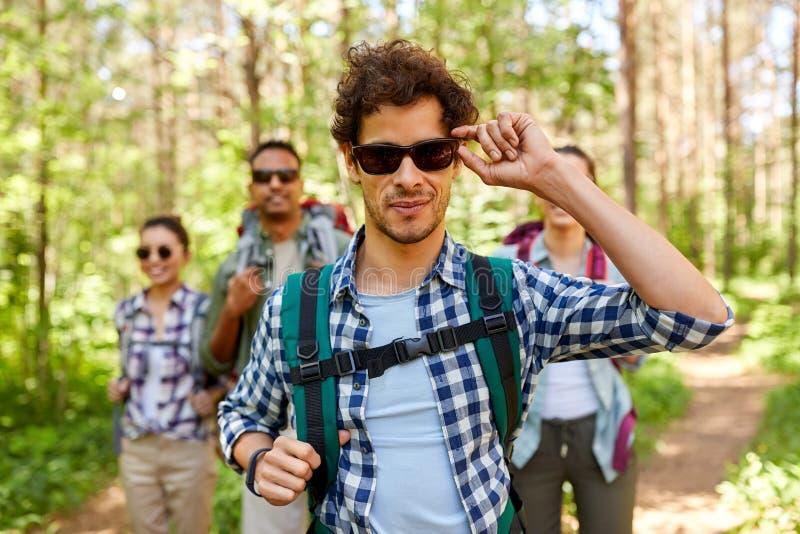 Freunde mit Rucksäcken auf Wanderung im Wald stockfotografie