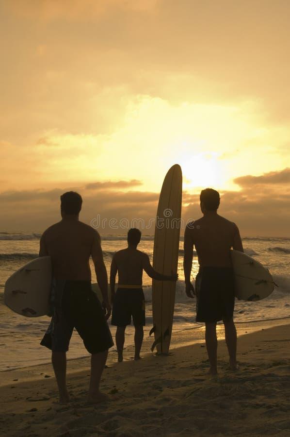 Freunde mit Surfbrett-aufpassendem Sonnenuntergang am Strand lizenzfreies stockfoto