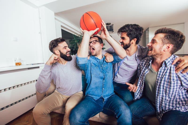 Freunde oder Basketballfans, die Basketballspiel im Fernsehen aufpassen und zu Hause Sieg feiern Freundschaft, Sport und lizenzfreies stockfoto
