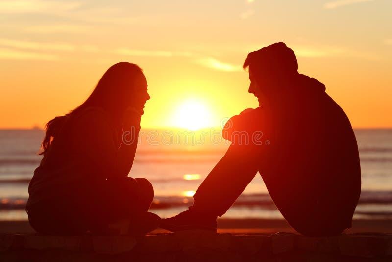 Freunde oder Paare des Teenagers, der bei Sonnenuntergang gegenüberstellt stockfotografie