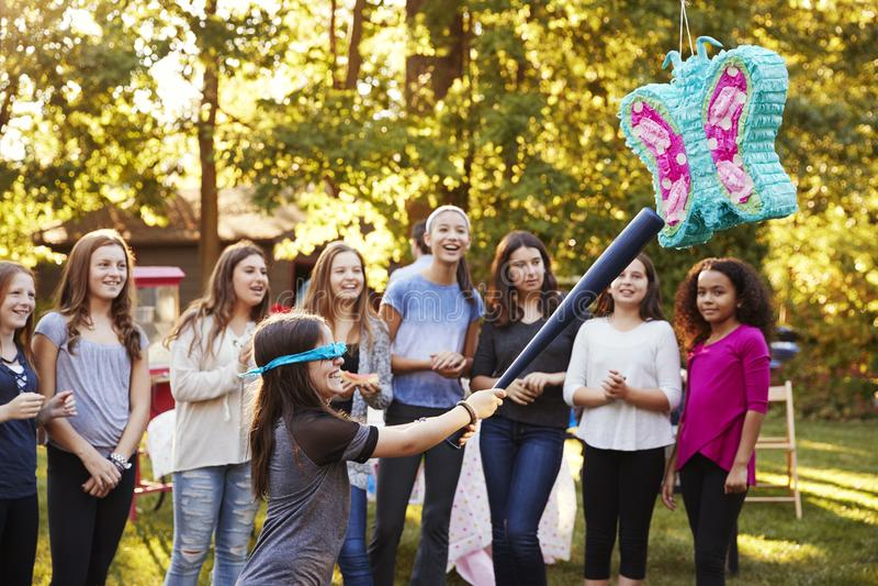 Freunde passen ein junges Mädchen auf, ein piï ¿ ½ ata auf ihrem Geburtstag zu schlagen lizenzfreie stockbilder