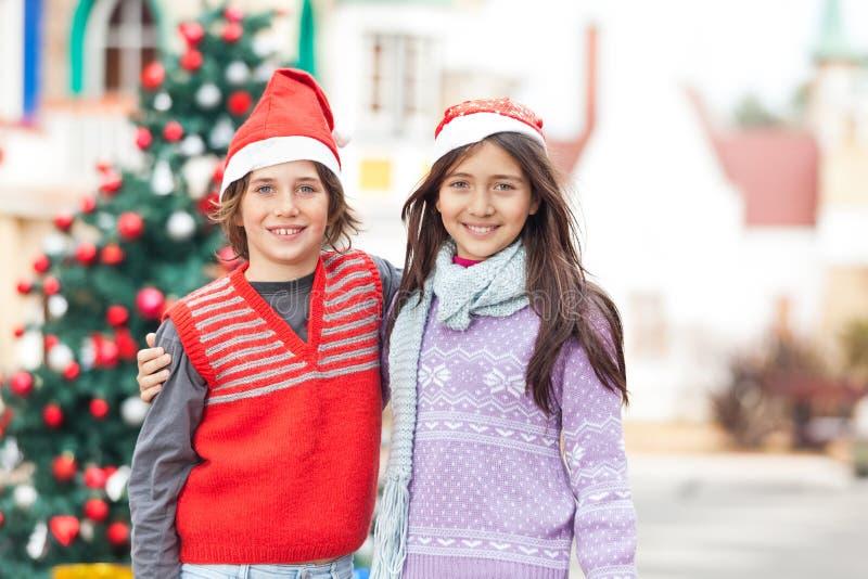 Freunde in Santa Hat Standing Against Christmas lizenzfreies stockfoto
