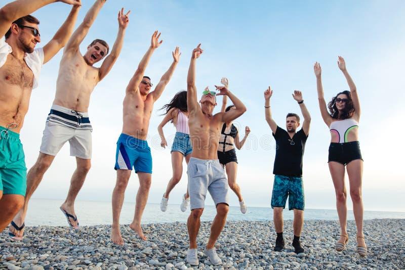 Freunde tanzen auf Strand unter Sonnenuntergangsonnenlicht und haben den Spaß, glücklich, genießen stockbilder
