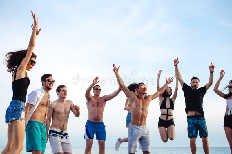 Freunde tanzen auf Strand unter Sonnenuntergangsonnenlicht und haben den Spaß, glücklich, genießen stockfotografie