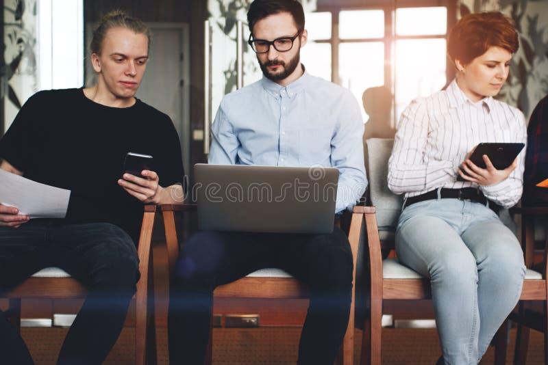 Freunde von den Mitarbeitern, die für moderne Geräte, smartp zusammenarbeiten stockbild