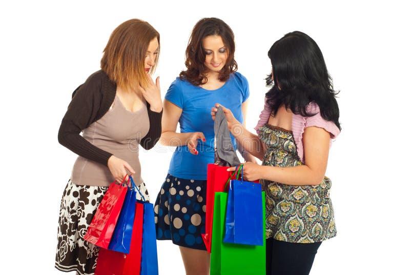Freundfrauen, die gekauftes Tuch betrachten stockbilder