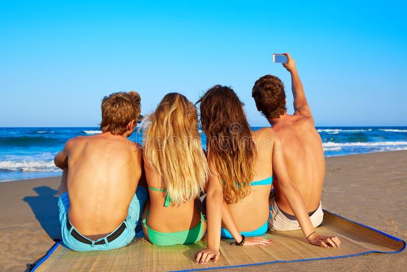 Freundgruppe selfie Foto, das im Strandsand sitzt lizenzfreies stockfoto