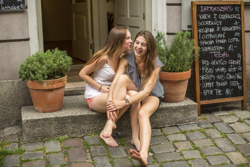 Freundin mit zwei jungen Mädchen, die auf den Schritten des Cafés und des Flüsterns sitzt lizenzfreie stockfotos