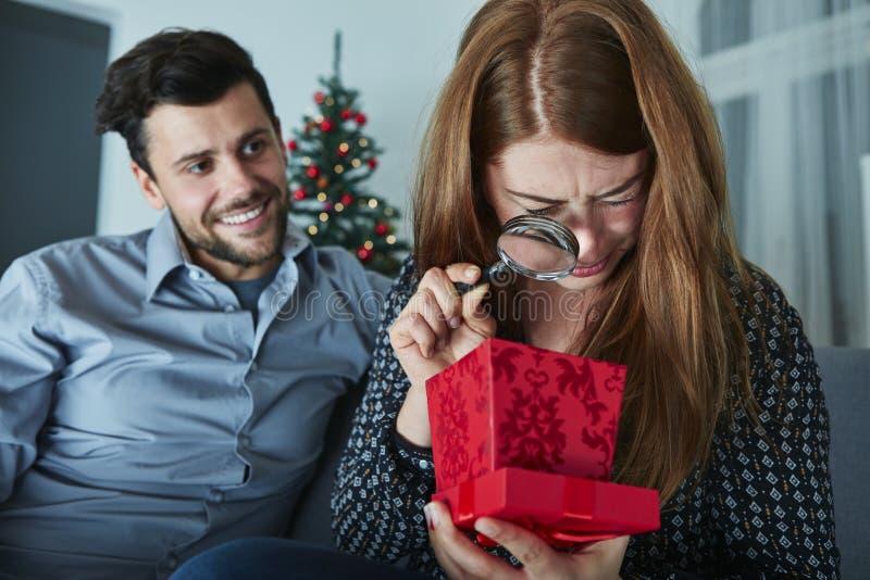 Freundin schaut zu ihrem Weihnachtsgeschenk skeptisch lizenzfreie stockfotografie