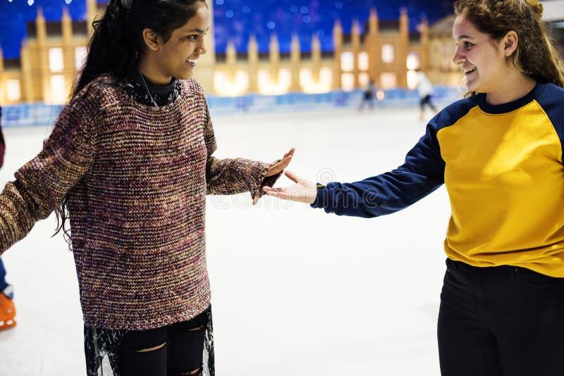 Freundineislauf auf der Eisbahn zusammen lizenzfreie stockbilder