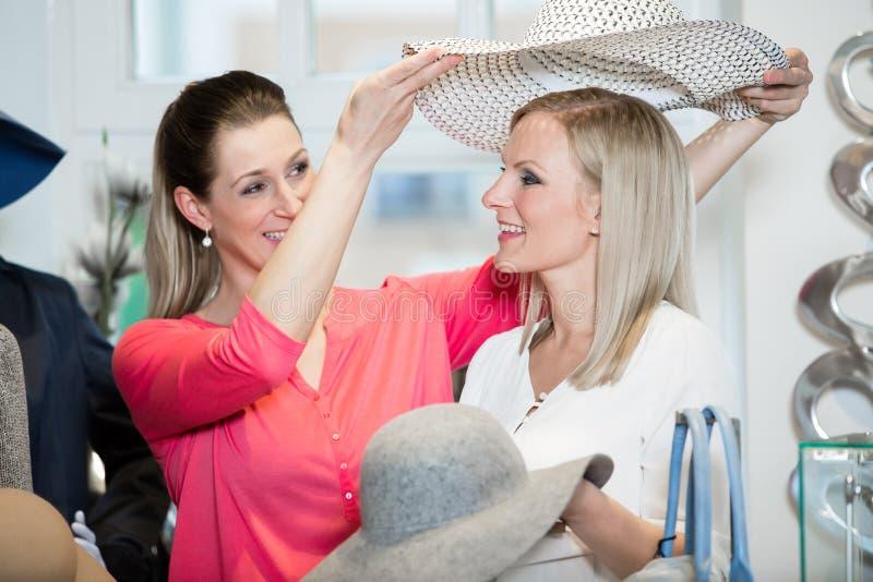 Freundinnen auf versuchenden Damenhüten shopping sprees und anderer Mode stockbilder