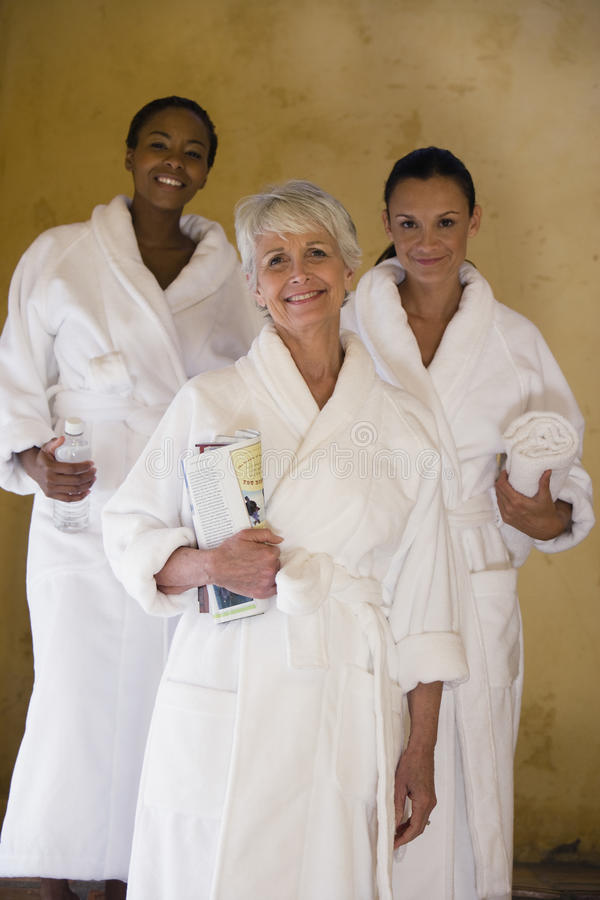 Freundinnen beim Bademantel-Lächeln lizenzfreie stockfotografie