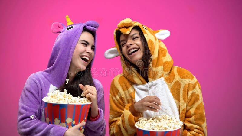 Freundinnen in den lustigen Pyjamas, die Spaß, werfendes Popcorn, Glück haben stockbilder