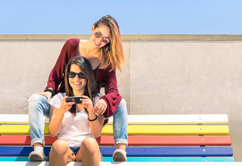 Freundinnen der besten Freunde, die zusammen Zeit draußen mit Smartphone genießen stockfoto