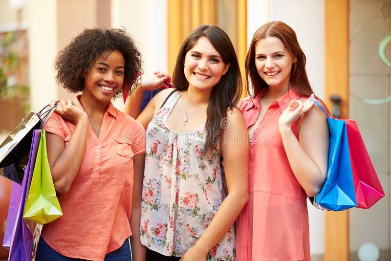 Freundinnen, die durch Mall mit Einkaufstaschen gehen stockbilder