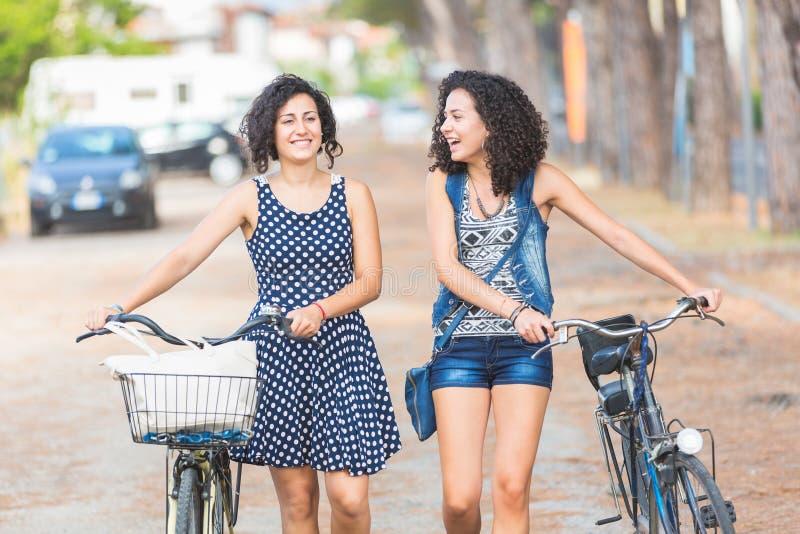 Freundinnen, die Fahrräder halten und in die Stadt gehen lizenzfreie stockfotografie