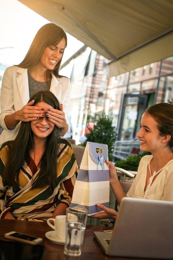 Freundinnen, die Geburtstagsgeschenk geben Mädchen überraschte ihren Freund lizenzfreie stockfotografie