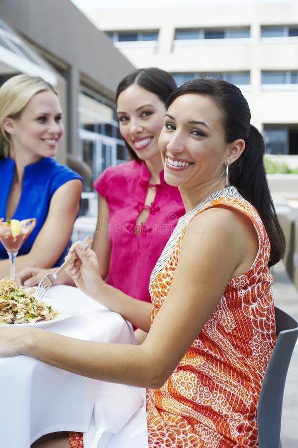 Freundinnen, die heraus zusammen essen stockbild