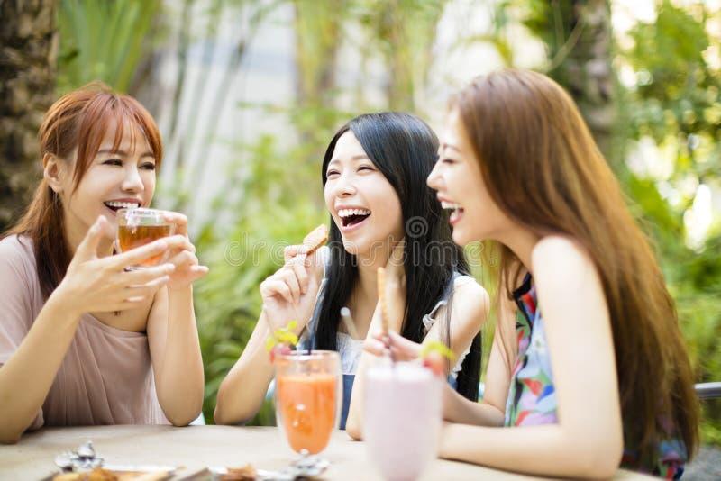 Freundinnen, die im Restaurantgarten sprechen stockfotografie