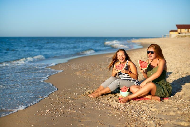 Freundinnen, die morgens frische Wassermelone an der Küste lachen und essen Zwei glückliche Freundinnen, die auf Tuch sitzen und stockfotos